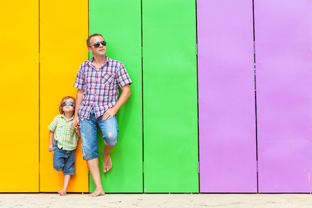 Father and son relaxing near the house at the day time. They standing near are the colorful wall. Concept of friendly family.
