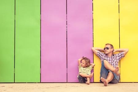 父と息子のリラックスした一日の時間で家の近きます。近くに座って彼らがカラフルな壁です。フレンドリーな家族の概念。 写真素材