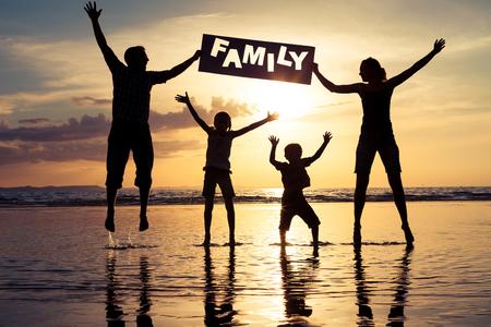 """일몰 시간에 해변에서 점프 행복 한 가족입니다. 부모는 손 비문 """"가족""""에서 개최합니다. 행복한 가족의 개념입니다."""