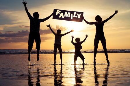 Happy family jumping on the beach at the sunset time. Parents hold in the hands  inscription Family. Concept of happy family. Banco de Imagens