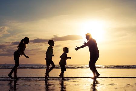 семья: Отец и дети, играющие на пляже во время заката. Концепция дружной семье.