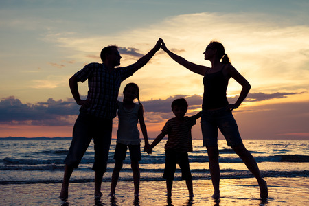 family together: Silhouette of happy family who playing on the beach at the sunset time. Concept of friendly family. Stock Photo