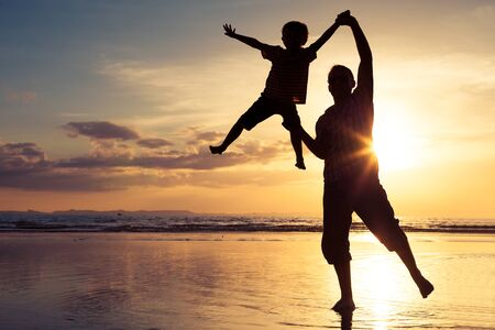 child couple: Father and son playing on the beach at the sunset time. Concept of happy friendly family.