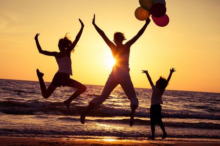 personas saltando: La madre y los niños jugando con globos en la playa en el momento de la puesta del sol. Concepto de la familia.