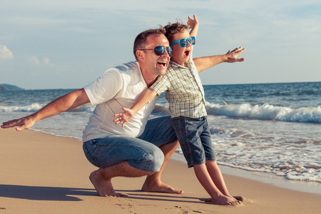 child couple: Father and son playing on the beach at the day time. Concept of friendly family.