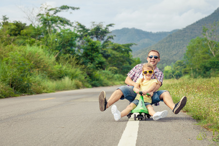 drive car: Father and daughter playing  on the road at the day time.  Concept of friendly family.