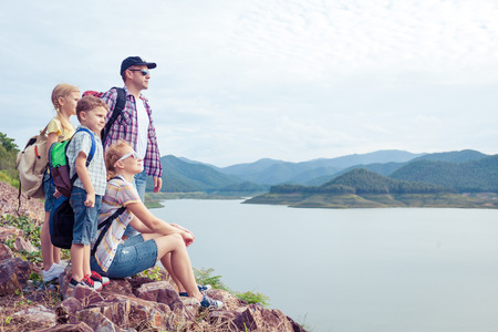 children sport: Happy family standing near the lake at the day time.  Concept of friendly family.