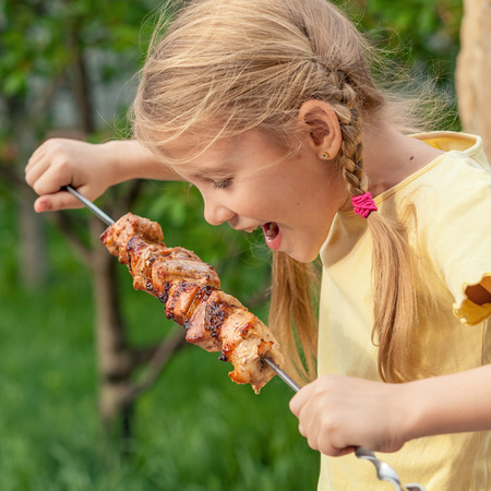 family outside: Little beautiful smiling girl  with pleasure eats shish kebab outdoor at the day time. Concept of healthy life.