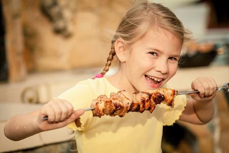 喜びと美しい笑みを浮かべて少女は、シシカバブ、昼は屋外を食べる。健康的な生活の概念。 写真素材