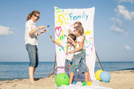 relaxing beach: Happy mother and children playing with paint on the beach at the day time. Concept of friendly family. Stock Photo