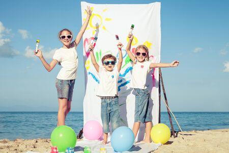 白天,三个孩子在海滩上玩颜料。概念兄妹永远在一起