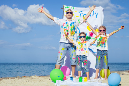 cool kids: Happy father and children playing with paint on the beach at the day time. Concept of friendly family.