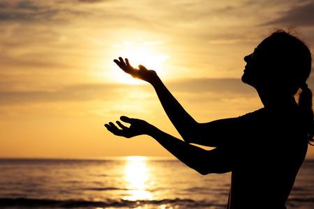 日没日でビーチで女性のシルエット。