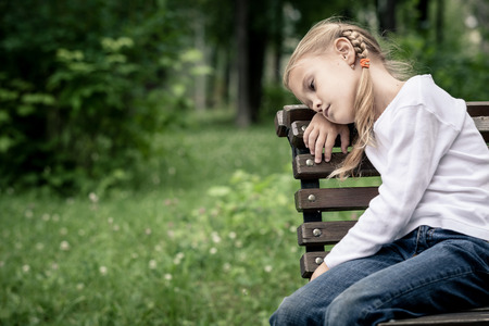 blond girl: Portrait of sad blond little girl sitting on bench at the day time.