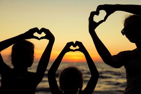 母と娘の日没時にビーチで遊んでいます。幸せなフレンドリーな家族の概念。