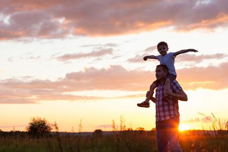 아버지와 아들 일몰 시간에 공원에서 연주. 친절 한 가족의 개념입니다. 스톡 콘텐츠