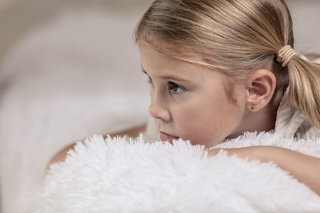 only girls: Portrait of sad little girl lying on bed at the day time. Concept of sad childhood. Stock Photo