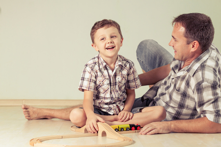kids having fun: Daddy with little boy playing with toy train on the floor at the day time. Concept of friendly family.