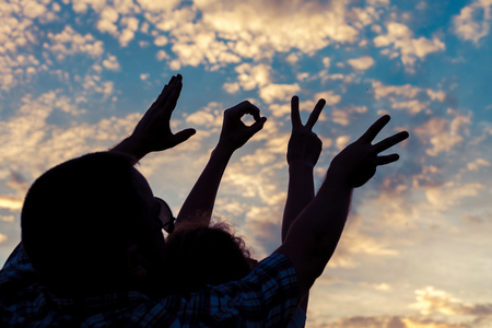 Aimez la langue des signes à l'heure du coucher du soleil. Concept de la famille sympathique et des vacances d'été. Banque d'images - 59288441