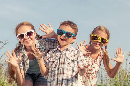 campamento: niños felices jugando en el campo en el tiempo del día. Concepto de hermanos amistosos de la familia.
