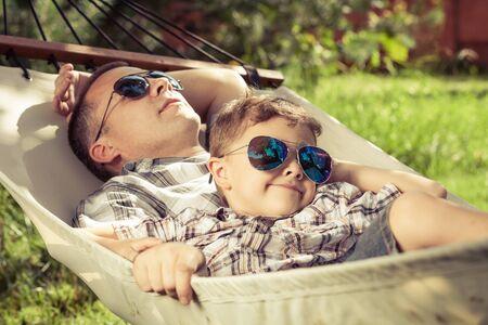 父と息子の日に庭でハンモックに横になっています。家族の性質上で楽しんで。フレンドリーな家族の夏休みの概念。