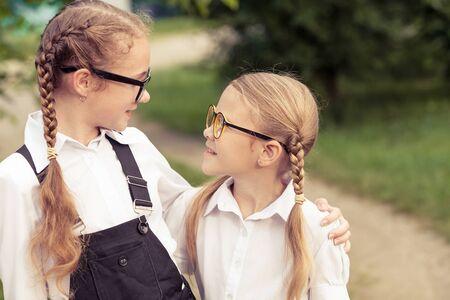Sonriendo jóvenes escolares en un uniforme escolar de pie contra un árbol en el parque en el tiempo del día. Concepto de las chicas está listo para ir a la escuela.