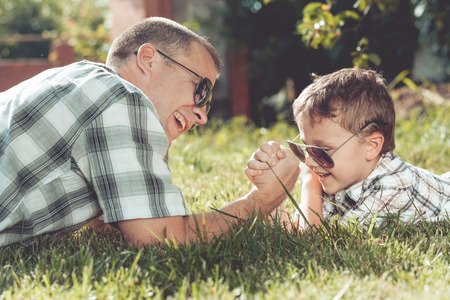 Father and son lying near a tree in the garden at the day time. Family having fun on the nature. Concept of friendly family and of summer vacation.