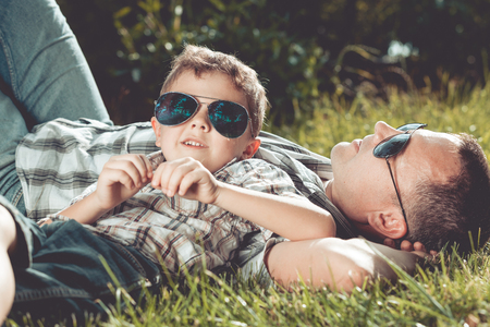 vacation summer: Father and son lying near a tree in the garden at the day time. Family having fun on the nature. Concept of friendly family and of summer vacation.