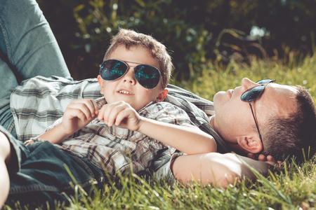 juventud: Padre e hijo tumbado cerca de un árbol en el jardín en el tiempo del día. Familia que se divierte en la naturaleza. Concepto de la familia y de las vacaciones de verano.