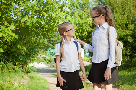 Smiling young school children in a school uniform standing against a tree in the park at the day time. Concept of the girls are ready to go to school. Stock Photo