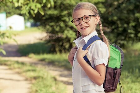 young students: Smiling young school child in a school uniform standing against a tree in the park at the day time. Concept of the child are ready to go to school. Stock Photo