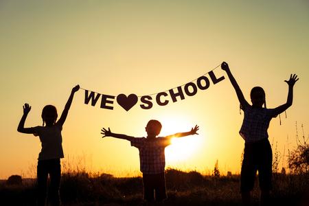 escuela primaria: Silueta de niños felices, que juegan en el campo en el momento de la puesta del sol. Ellos se divierten en la naturaleza. Concepto de los niños están listos para ir a la escuela.