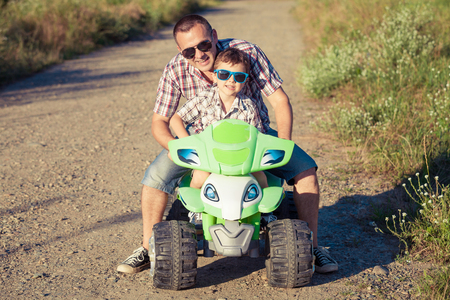 Father and son playing on the road at the day time. They driving on quad bike in the park. People having fun on the nature. Concept of friendly family. Stock Photo