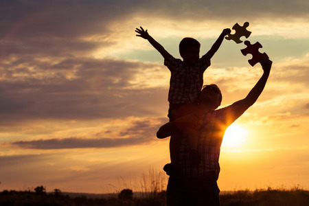 父と息子の日没の時に公園で遊ぶ。人々 は、フィールド上で楽しんで。子供の概念は学校に行く準備ができています。