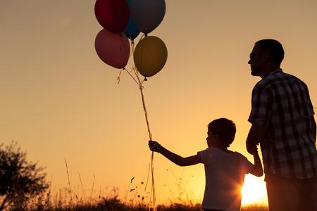 pareja en casa: Padre e hijo jugando en el parque a la hora del atardecer. La gente que se divierte en el campo. Concepto de la familia y de las vacaciones de verano. Foto de archivo
