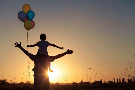 일몰 시간에 공원에서 풍선을 가지고 노는 아버지와 아들. 사람들은 필드에 재미. 친화적 인 가족의 여름 휴가의 개념.