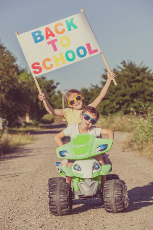Happy little children playing on road at the day time. They driving on quad bike in the park. People having fun on the nature. Concept of the kids are ready to go to school.