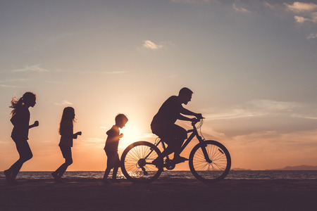 family vacation: Father and children playing on the beach at the sunset time. People having fun on the sea. Concept of friendly family and of summer vacation.