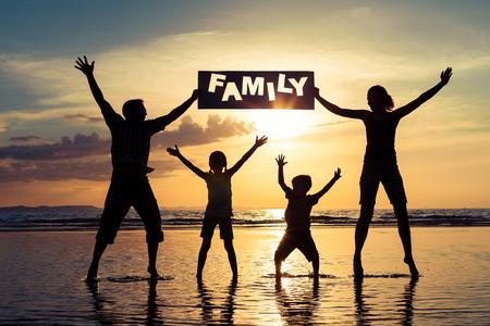 누가 일몰 시간에 해변에 서있는 행복 한 가족의 실루엣. 사람들은 바다에서 재미입니다. 우정의 영원과 여름 휴가의 개념입니다. 스톡 콘텐츠