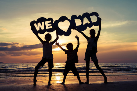 Happy children playing on the beach at the sunset time. Kids hold in the hands inscription We love dad. Concept of happy father day.