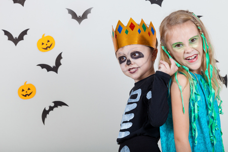 Happy brother and  sister on Halloween party. People having fun indoor. Children wearing costumes  skeletons and witches. Concept of children ready for a party. Stock Photo