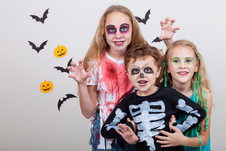 Happy brother and two sisters on Halloween party. People having fun indoor. Children wearing costumes zombies, skeletons and witches. Concept of children ready for a party.