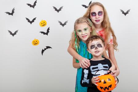 행복 한 형제와 두 자매 할로윈 파티에. 사람들은 실내에서 재미입니다. 아이들은 의상 좀비, 해골과 마녀를 입고. 어린이위한 파티 준비의 개념입니다
