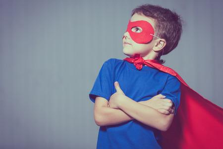 Glückliches kleines Kind spielt Superheld. Kid Spaß im Freien. Konzept der Junge Macht. Standard-Bild