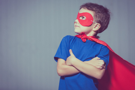 Happy little child playing superhero. Kid having fun outdoors. Concept of boy power. Stock Photo