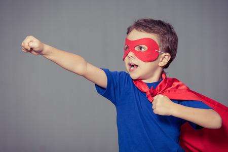 boy kid: Happy little child playing superhero. Kid having fun outdoors. Concept of boy power. Stock Photo