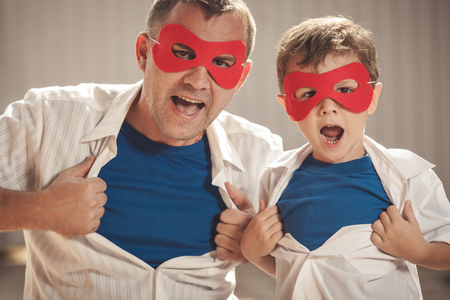 父亲和儿子在白天演奏超级英雄。人们在户外玩得开心。友好的家庭的概念。