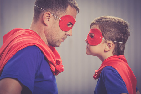 Father and son playing superhero  at the day time. People having fun outdoors. Concept of friendly family. Stock Photo