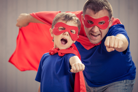 Father and son playing superhero  at the day time. People having fun outdoors. Concept of friendly family. Archivio Fotografico