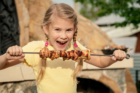 Little beautiful smiling girl with pleasure eats kebab outdoor at the day time. Child having fun near a house. Concept of healthy life.